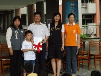 一年級小學弟呈師生家長保留珍貴老樹連署書給副議長邱芳欽。(宣信國小提供)