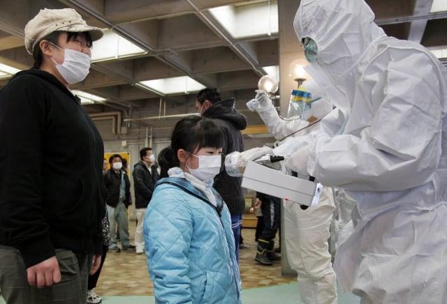 日本近日一項調查發現,福島有59名孩童得了甲狀腺癌,發病率高出全日本數十倍。圖為2011年3月為福島災區居民檢測輻射值。(AFP)