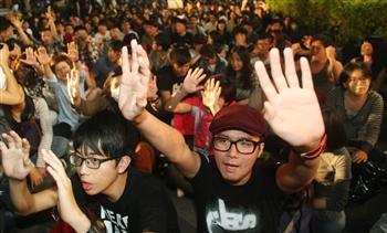 反服貿民眾19日持續占據立法院議場,場外群集民眾因現場騷動而鼓噪,主持人要大家高舉雙手、保持和平理性。(中央社)