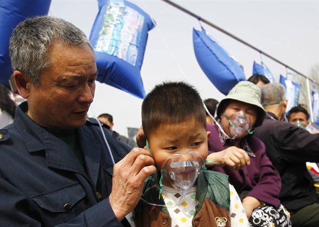 當地時間3月29日,河南鄭州的廣場上,新鮮袋裝空氣被用來宣傳旅遊項目,反響頗佳,小孩也戴上呼吸面罩參加。內陸城市空氣質量低下程度,由此可見一斑(AFP)