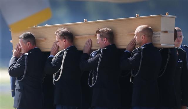 荷蘭軍方抬著MH17 罹難者遺體莊嚴的走下飛機。(Peter Macdiarmid/Getty Images)