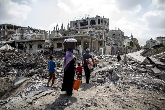 以巴雙方承諾72小時停火後,一名巴勒斯坦人帶著家人回到加薩,尋找被破壞的家。(AFP)