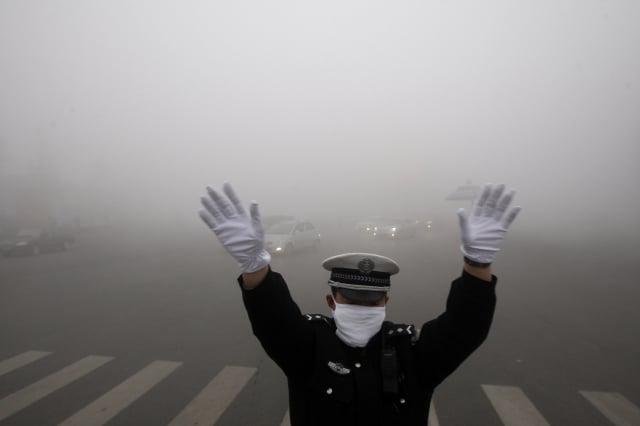 紀錄片《穹頂之下》展示中國各地嚴重的霧霾汙染。圖為去年10月22日,哈爾賓霧霾嚴重,交警在路上指揮交通。(AFP)