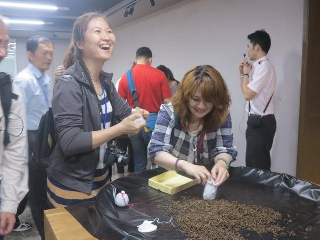 「遊山茶訪」觀光工廠的訪客開心地親手製作小茶包。(攝影/鄧玫玲)