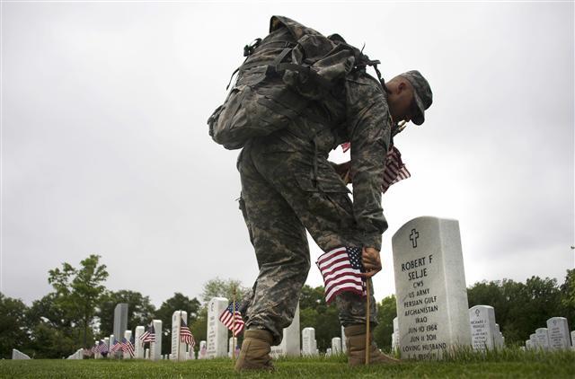 美國陣亡將士紀念日,美國陸軍第三步兵團的士兵在阿靈頓國家公墓在陣亡將士墓碑前插上美國國旗。(JIM WATSON / AFP)