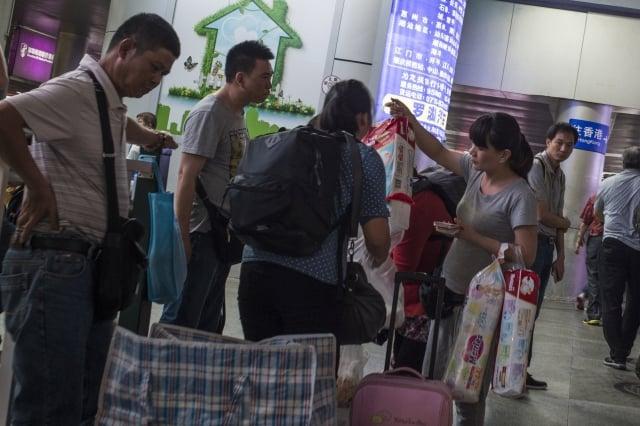 陸客在香港搶購奶粉、日本搶購免治馬桶,造成不良觀感。圖為陸客赴港購物畫面。(AFP)