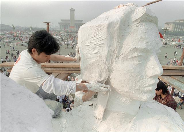1989年5月30日,一名學生在天安門廣場雕刻「民主女神」雕像。該雕像僅用四天時間便趕製而成,由中央美術學院雕塑系、北京電影學院、中央戲劇學院、中央音樂學院、中國音樂學院、中央工藝美術學院、北京舞蹈學院等八所院校的共二十多位學生合製而成。雕像聳立在天安門城樓南300米處,與門洞上方的毛澤東肖像對望。四天後,即6月4日凌晨五時左右,被前來清場的解放軍部隊用推倒,過程被記者拍攝下來。(記者CATHERINE HENRIETTE / AFP/攝影)