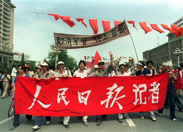 1989年5月22日,人民日報的記者也加入天安門廣場遊行行列,舉著「取消軍管、保衛首都」的口號。(CATHERINE HENRIETTE / AFP)