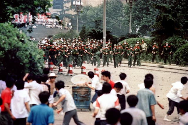 1989年6月4日,北京的學生和市民向進逼的軍隊丟擲石頭。(AFP)