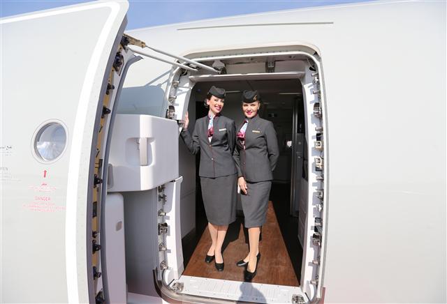 空服員在起飛降落時都要確保機門緊急滑梯調到正確的位置。圖為卡達航空的空服員。(KARIM JAAFAR / AL-WATAN DOHA / AFP)