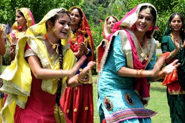 印度法院做出里程碑裁決,認長女可繼承家業。圖為印度大學女生穿上傳統服裝,跳舞慶祝雨季到來。(AFP)