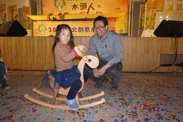 木作達人林昭賢(右)望著小朋友騎玩自己創作的木馬作品,感到很開心。(記者李怡欣/攝影)