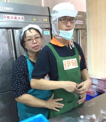 身障學員小翔媽張淑君現身活動,與小翔一起包裝餅乾。(記者徐乃義/攝影)