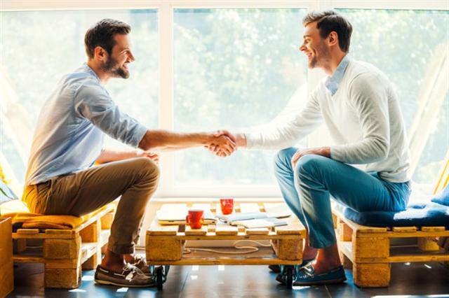 男子握手。两个幸福的年轻男子握手,而坐在窗前侧视图(fotolia)