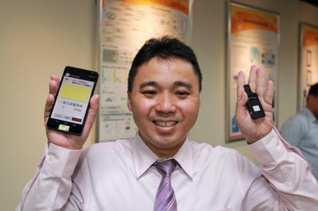 國家奈米元件實驗室組長薛丁仁右手拿著已安裝智慧型氣體感測晶片的手機,左手則是酒精感測鑰匙圈。(國研院提供)