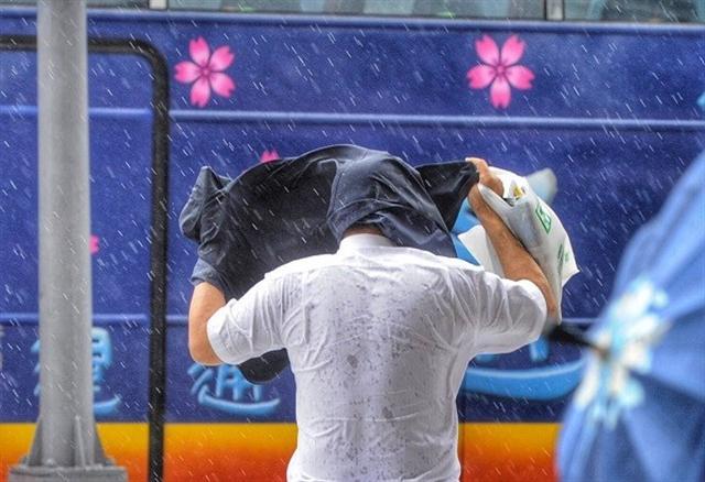 中度颱風梅姬侵襲台灣,27日上午台北市已出現間歇的風雨。(中央社)