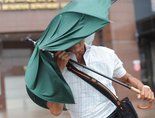 中度颱風梅姬侵襲台灣,27日上午台北市已出現間歇的風雨,路上民眾奮力抗強風。(中央社)