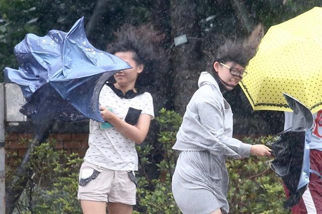 中度颱風梅姬威脅台灣本島及離島,27日上午各地風雨逐漸明顯,中央氣象局預測,午後颱風中心在花東交界登陸,風雨會更強。走在台北街頭的民眾撐傘,仍抵擋不住強風的吹襲。(中央社)