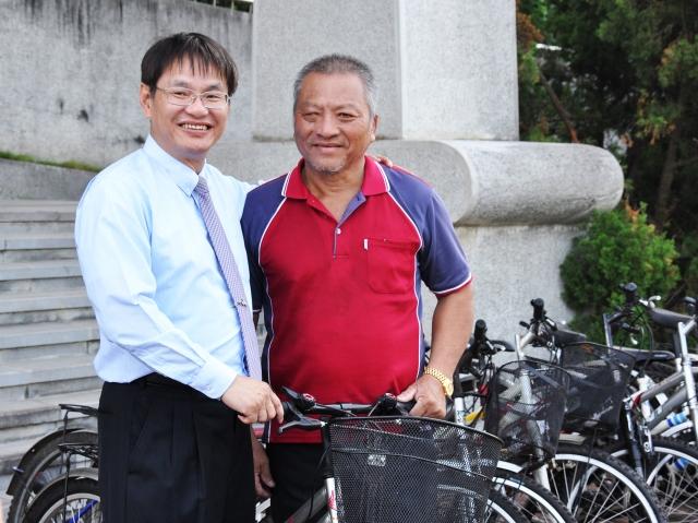 中正大學校長馮展華(左)親自將校內30輛二手單車交給上林社區發展協會理事長陳煦湘(右),希望共同促進地方輕旅。(中正大學提供)