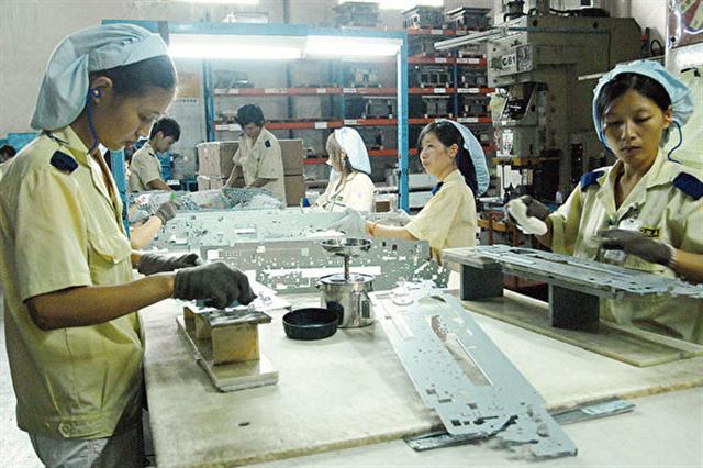 製造業台商在中國經營環境日趨惡劣,紛紛撤離。圖為東莞台商工廠的女作業員。(AFP)