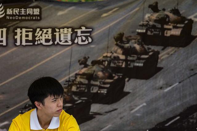 圖為2016年6月4日一位中國民主運動人士坐在香港紀念1989年天安門廣場六四鎮壓事件攤位前的「坦克人」照片海報前面。 (ANTHONY WALLACE/AFP/Getty Images)