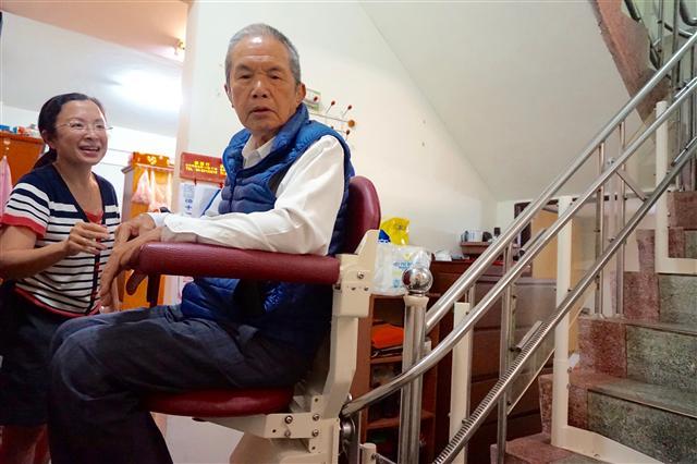 騰城樓梯升降椅在品質上獲得肯定,其商用何小姐開心看何伯伯示範樓梯升降椅。(騰城科技提供)