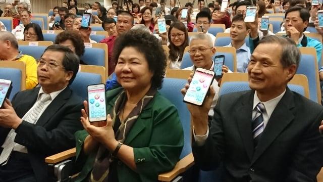 高市長陳菊(右二)與高市消防局長陳虹龍(右一),向民眾推廣示範報案APP。(記者李怡欣/攝影)