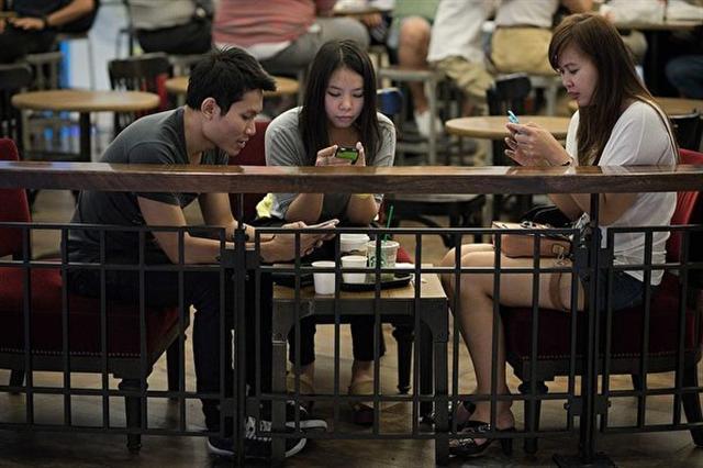 朋友在咖啡廳聚會,但是滑手機佔據了見面交流的時間。(NICOLAS ASFOURI/AFP/Getty Images)