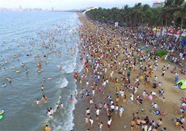 今年夏季中國大陸酷熱,很多人早早的就去海邊。圖為5月30日的海口海灘。(Getty Images)