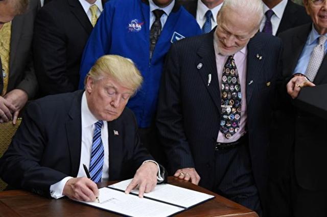 美國總統川普6月30日簽署行政令,重建國家航天委員會。阿波羅11號登月太空人布茲·奧爾德林(Buzz Aldrin)(右)在一旁見證川普的簽署。(Olivier Douliery-Pool/Getty Images)