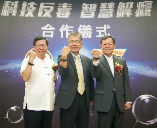 左起桃園市長鄭文燦、中大校長周景揚和中華民國解癮戒毒協會理事長華琳穿戴中大研發的智慧手環,一同運用科技反毒。