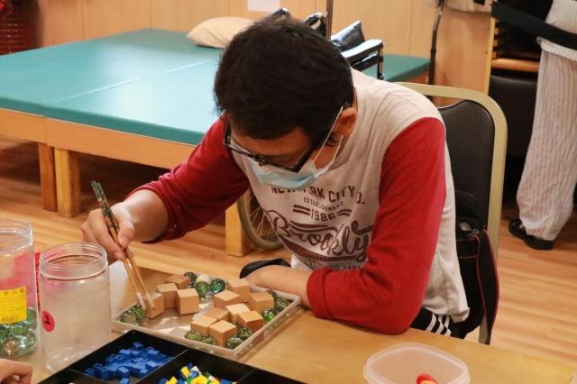 陳先生以筷子夾積木、玻璃珠等做復健,練習手指靈活度與肌力。(台中慈濟醫院提供)