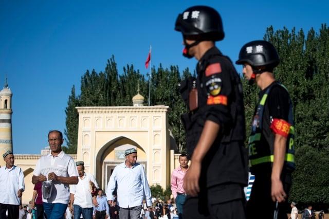 中共當局被曝收集新疆居民的DNA樣本、存入資料庫。圖為中共警察在新疆一清真寺外。(Getty Images)