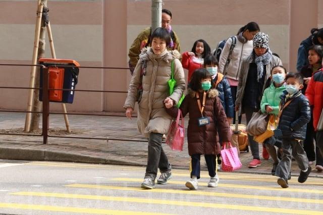 香港爆發流感,教育局宣布幼稚園及小學提前放新年假。圖為家長接子女放學情況。(記者陳仲明/攝影)