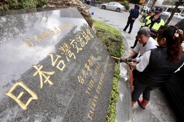 日本台灣交流協會7日遭一名年約50歲的男子潑紅漆,警方到場後將他逮捕,清潔人員也迅速將紅漆沖洗乾淨,現場員警戒備。(中央社)