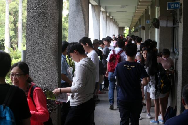 107學年度大學指考1日登場,首日考物理、化學、生物,學生在走廊溫習功課,做考前最後衝刺。