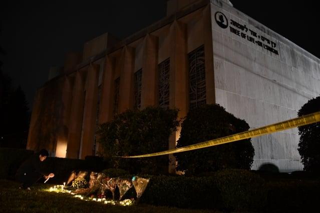 週六上午10時左右,美國賓州匹茲堡市松鼠丘附近的「生命之樹」猶太教堂發生重大槍擊案,11人死亡、6人受傷,槍手當場被捕。圖為民眾向受難者致意。(BRENDAN SMIALOWSKI/AFP/Getty Images)