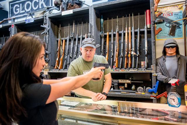 美國民間擁槍的傳統由來已久,擁槍的權力是憲法保護的。圖為在商店買槍的美國民眾。(EMILY KASK/AFP/Getty Images)
