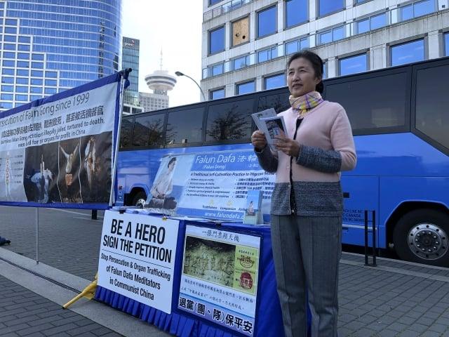 王俊華在溫哥華市中心向行人派發資料、講述法輪功真相。(記者陳璐/攝影)