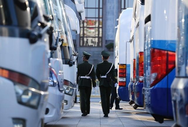 經常有訪民進京上訪後被送往馬家樓、久敬莊,圖為警察行走在警車之間。(Getty Images)