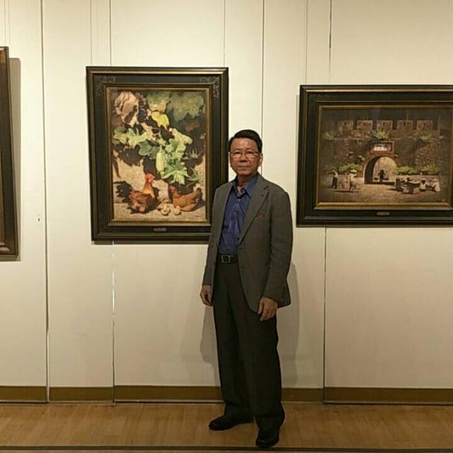 陳文福與其畫作合影。