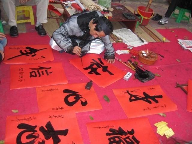 越南老宿儒會在春節的時候席地而坐彎腰趴下用毛筆寫揮春。(維基百科)