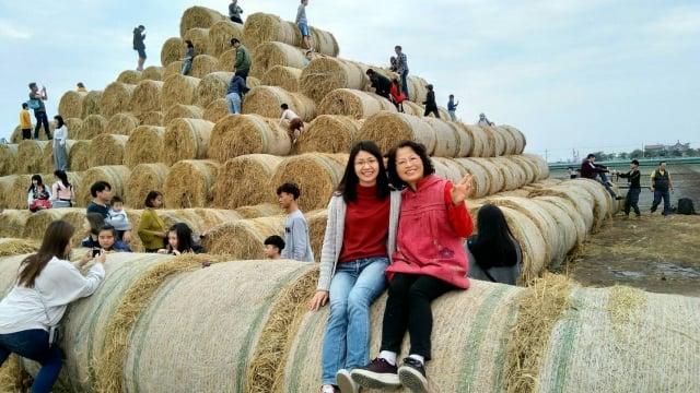 遊客在稻草捲心酥前開心留影。