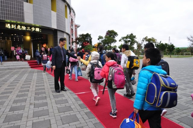開學日興隆國小學童走紅毯進入校園,校長徐發斌親自迎接和孩子打招呼(記者賴月貴/攝影)