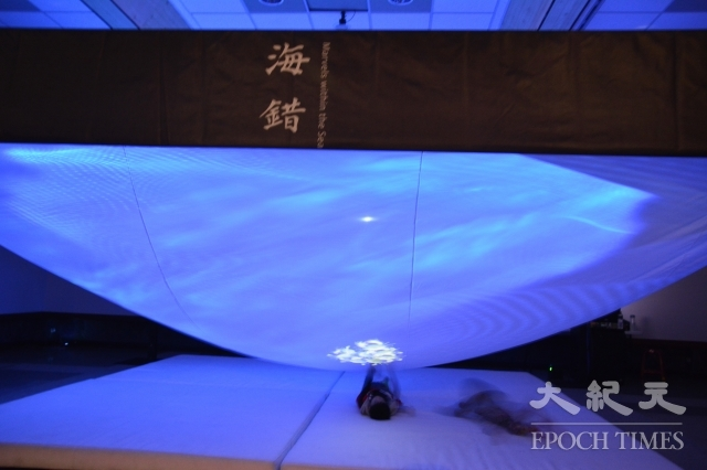 海錯圖沉浸式互動劇場,民眾以躺臥觀賞方式,手觸頂上的布幕與魚類互動。