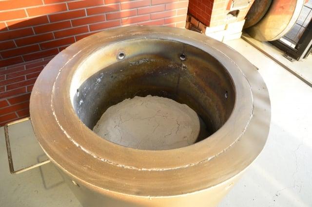 文火炭焙要將碎炭鏟入爐中均勻鋪平後,引火後把木炭燒紅後再蓋上炭灰,之後每小時翻茶一次,大概需要10天慢火才能烘焙完成。(攝影/鄧玫玲)