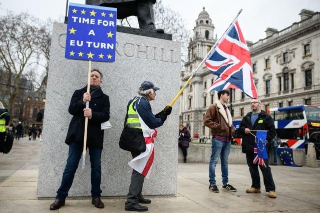 圖為1月15日,英國倫敦下議院的邱吉爾雕像前,一名支持留歐人士和一名支持脫歐的人士舉著旗幟或標語。(Getty Images)