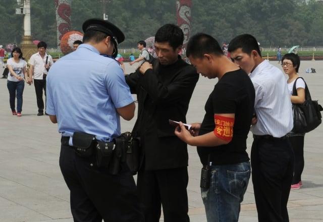 中國第三代身分證加入了定位及蒐集個人指紋和血液資訊等新功能。圖為公安在檢查民眾身分證。(Getty Images)