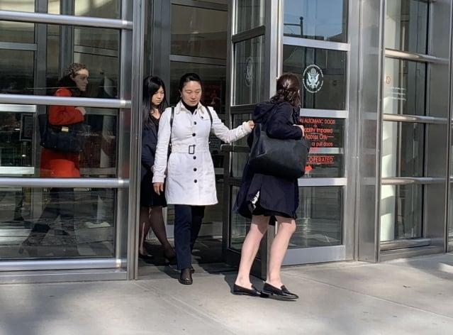 林英(白外套)和律師(紅外套)走出法庭。(記者蔡溶/攝影)