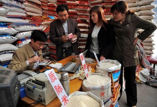 貿易戰關鍵時刻,中共下令全面展開中國性糧食庫存數量和品質大清查。有學者認為,中共正在防範糧食危機。圖為上海一家糧食批發市場糧販正在賣糧計價。(Getty Images)